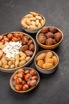Vue de face de différentes noix noix fraîches à l'intérieur de pots sur surface grise