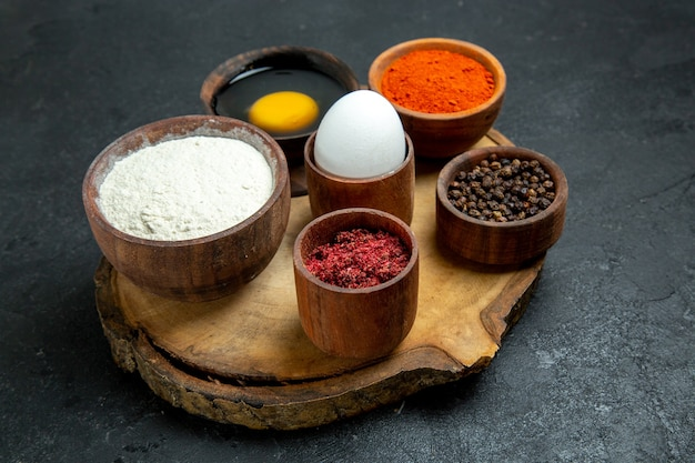 Vue de face différents assaisonnements avec de la farine et des œufs sur un espace gris
