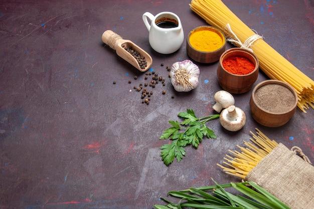 Vue de face différents assaisonnements avec des pâtes crues et des champignons sur une surface sombre repas de produits alimentaires crus