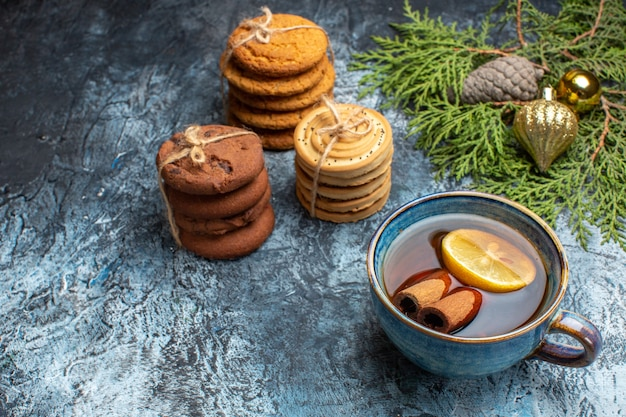 Vue de face différents biscuits sucrés avec tasse de thé sur fond clair