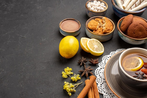 Vue de face différents biscuits avec tasse de thé et tranches de citron sur fond sombre biscuits biscuit aux agrumes sucre de fruits