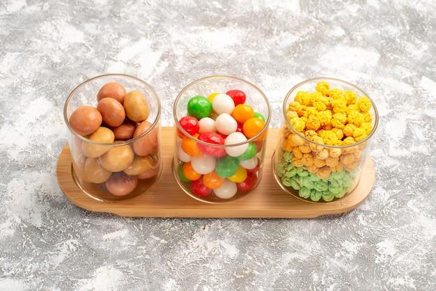 Vue de face différents bonbons bonbons colorés sur un espace blanc