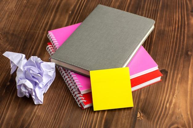 Vue de face différents cahiers colorés sur la surface brune