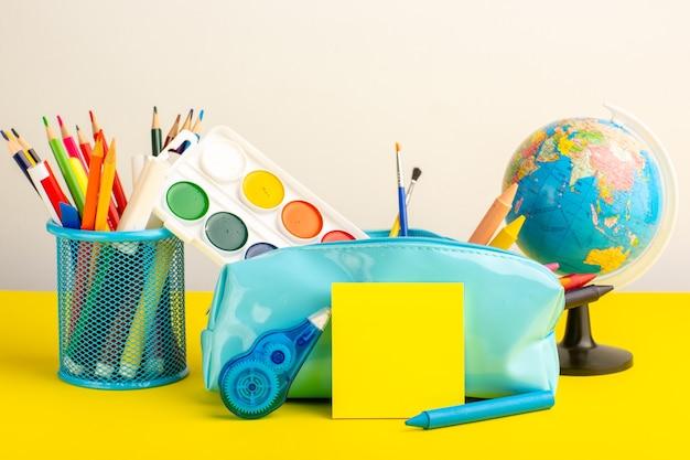 Vue de face différents crayons et peintures colorés à l'intérieur de la boîte de stylo bleu sur le bureau jaune