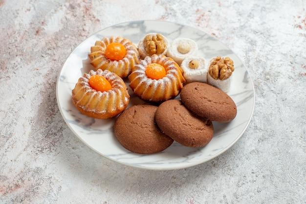 Vue de face différents gâteaux petits bonbons sur un espace blanc