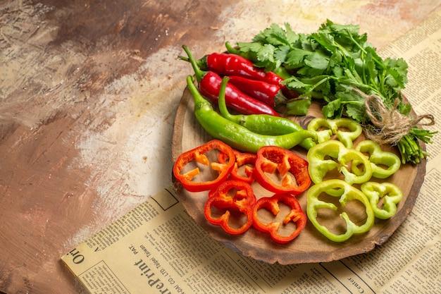 Vue de face différents légumes coriandre piments forts poivrons coupés en morceaux sur une planche de bois d'arbre rond un journal sur fond ambre avec espace de copie
