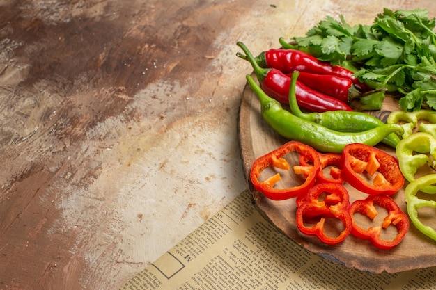 Vue de face différents légumes coriandre piments forts poivrons coupés en morceaux sur une planche de bois d'arbre rond