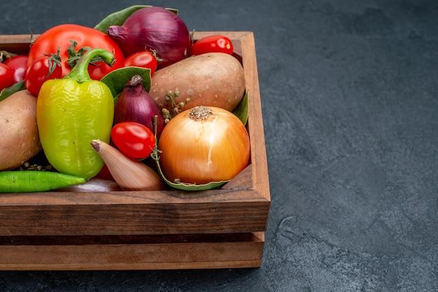 Vue de face différents légumes frais sur table sombre salade fraîche de légumes mûrs