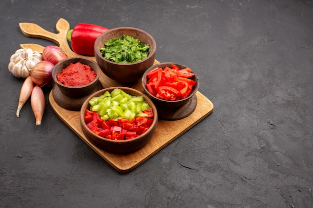Vue de face différents légumes avec des verts sur fond gris repas salade santé mûr épicé