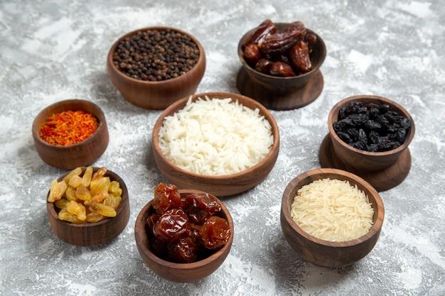 Vue de face différents raisins secs avec assaisonnements et riz sur un espace blanc