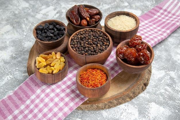 Vue de face différents raisins secs avec khurma et riz sur un espace blanc