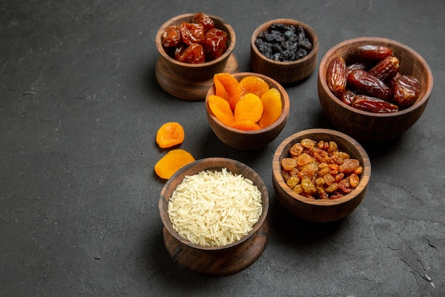 Vue de face différents raisins secs avec khurma sur une surface grise aux raisins secs aux fruits secs