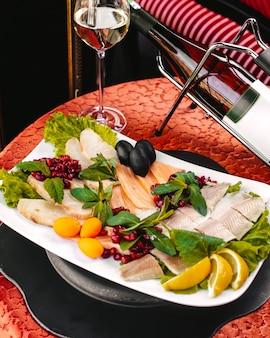 Une vue de face différents repas de fruits de mer à l'intérieur de la plaque blanche avec des feuilles vertes et des citrons en tranches sur la table
