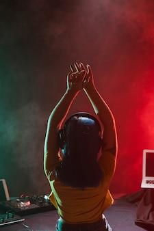 Vue de face dj féminin avec les mains levées au-dessus de la tête