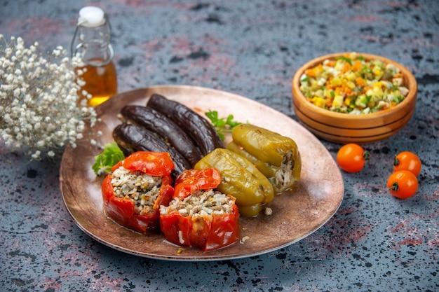 Vue de face dolma d'aubergine avec tomates cuites et poivrons farcis de viande hachée à l'intérieur de la plaque sur fond bleu