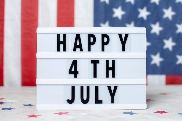 Vue de face drapeau usa avec signe du 4 juillet heureux
