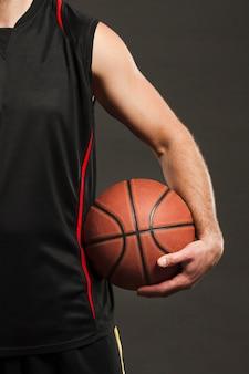 Vue de face du ballon de basket tenu par le joueur près du corps
