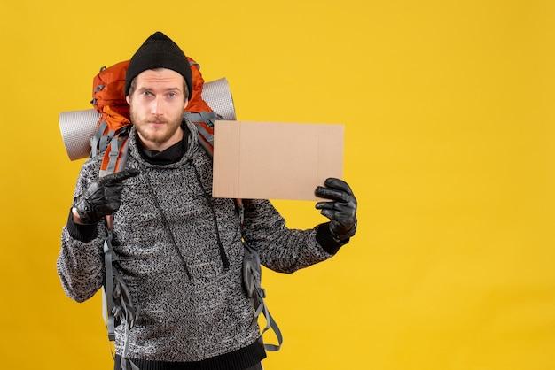 Vue de face du beau auto-stoppeur avec des gants en cuir et sac à dos pointant sur carton vierge