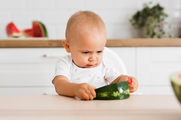 Vue de face du beau bébé mangeant de la pastèque