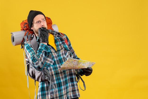 Vue de face du beau jeune touriste avec des gants en cuir et sac à dos tenant la carte
