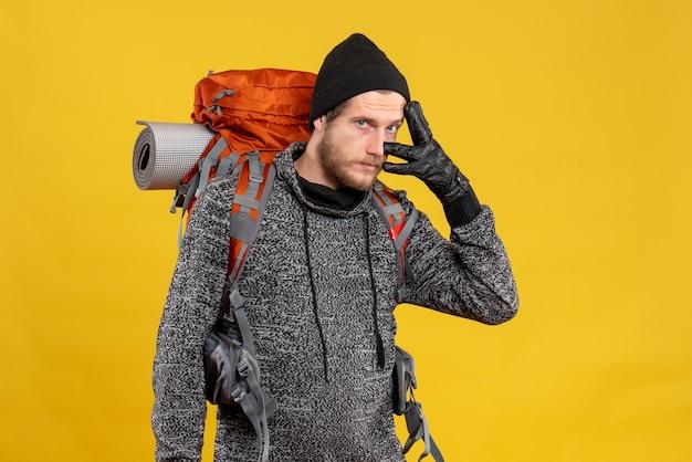 Vue de face du beau mâle auto-stoppeur avec des gants en cuir et sac à dos debout sur le mur jaune
