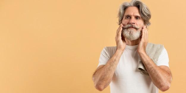 Vue de face du bel homme âgé avec barbe et espace copie