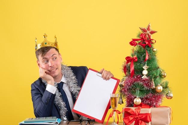 Vue de face du bel homme avec couronne assis à la table près de l'arbre de noël et présente sur jaune