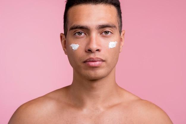 Vue de face du bel homme avec crème pour le visage sur