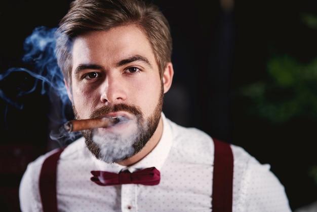 Vue de face du bel homme fumant un cigare cubain