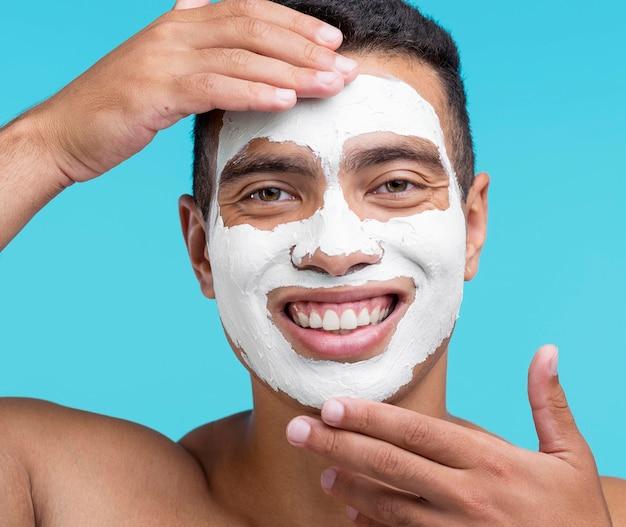 Vue de face du bel homme souriant avec un masque de beauté sur