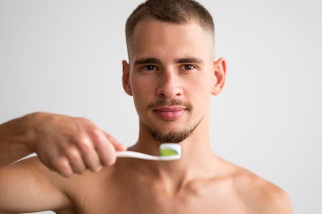 Vue de face du bel homme tenant une brosse à dents avec du dentifrice dessus