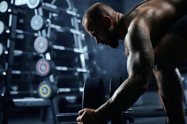 Vue de face du bodybuilder barbu mettant des poids sur haltères.