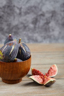 Vue de face du bol de figues noires et tranches de figues sur table en bois.