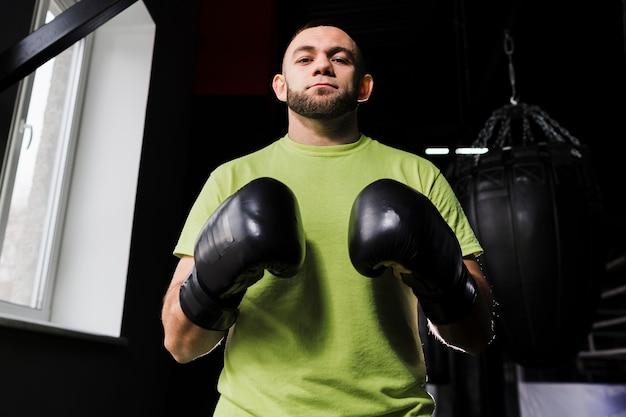 Vue de face du boxeur masculin portant des gants de protection et un t-shirt