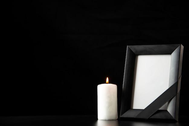 Vue de face du cadre photo avec bougie blanche sur le noir