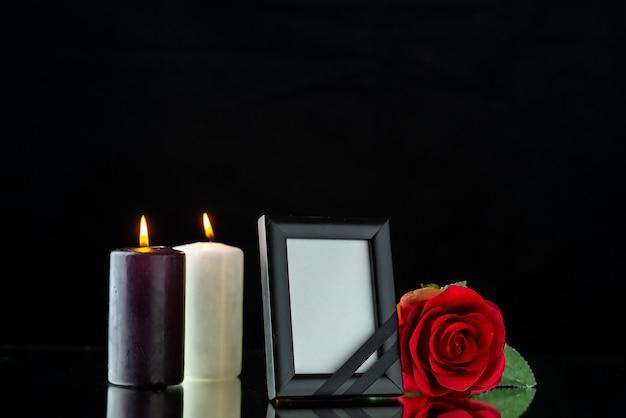 Vue de face du cadre photo avec bougie et rose rouge sur fond noir