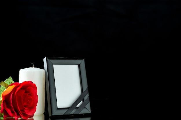 Vue de face du cadre photo avec bougie et rose rouge sur noir