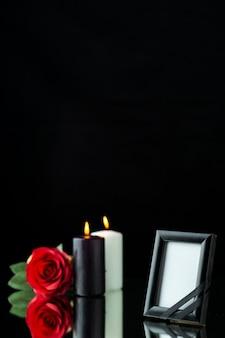 Vue de face du cadre photo avec bougies et rose rouge sur fond noir