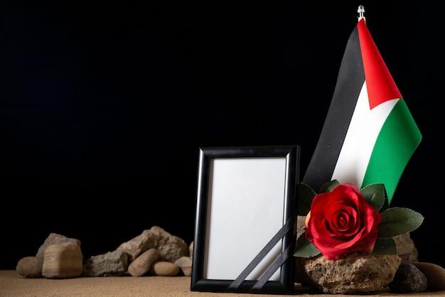 Vue de face du cadre photo avec fleur rouge et pierres sur fond noir