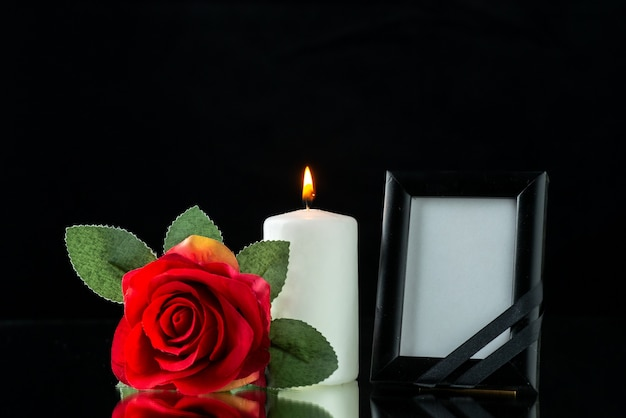 Vue de face du cadre photo avec rose rouge sur fond noir