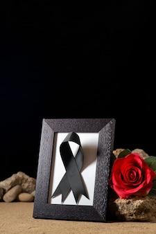 Vue de face du cadre photo vide avec fleur rouge et pierres sur fond noir