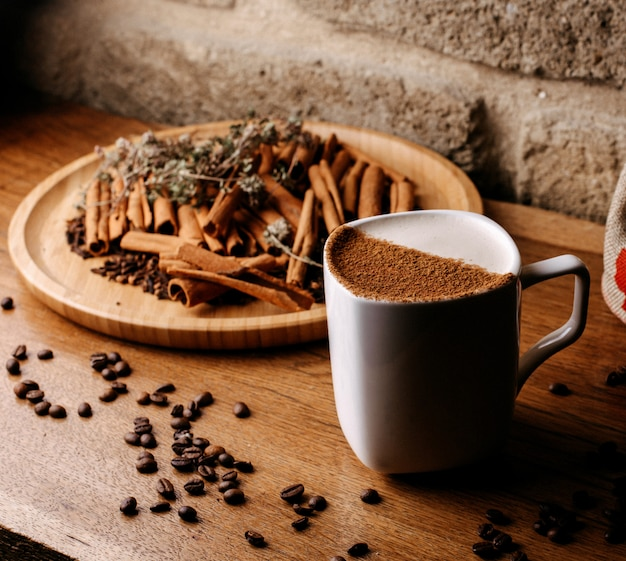 Vue de face du café à l'intérieur de la tasse blanche avec des graines de café et de la cannelle