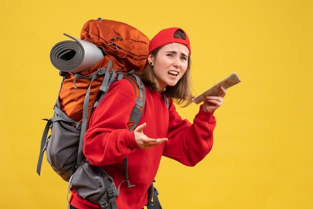 Vue de face du campeur féminin avec sac à dos rouge tenant la carte de voyage