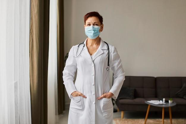 Vue de face du centre de récupération des aînés covid femme médecin avec masque médical