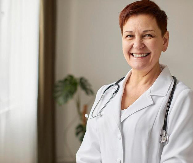 Vue de face du centre de récupération de covid smiley aîné femme médecin