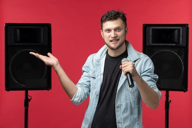 Vue de face du chanteur sur scène sur le mur rouge