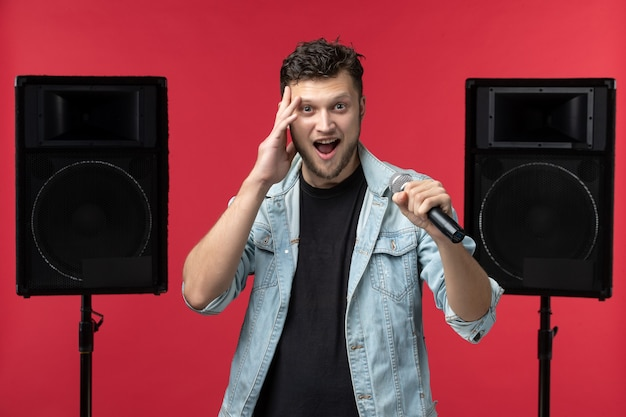 Vue de face du chanteur sur scène avec système stéréo sur le mur rouge