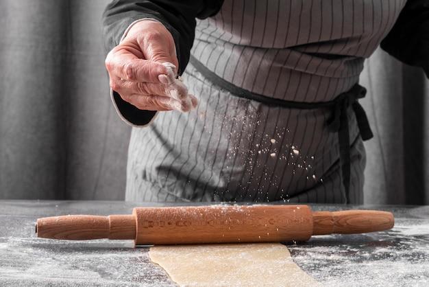 Vue de face du chef féminin à l'aide de farine pour rouler la pâte