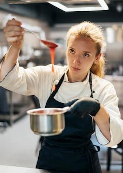 Vue de face du chef féminin préparant la sauce