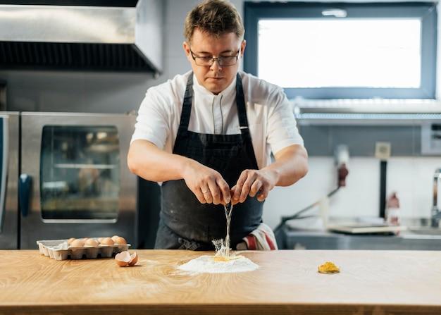 Vue de face du chef masculin casser l'oeuf sur la farine pour créer de la pâte